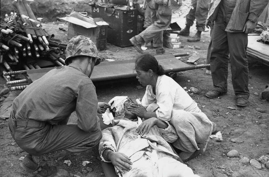 After the American invasion and bombardment of Inchon, South Korea, a civilian casualty receives treatment from a US medical orderly. Photo: Bert Hardy, Getty Images / Picture Post