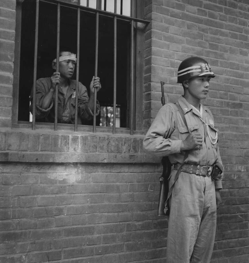 A South Korean soldier guards the Taegu Mission School which is being used as a POW camp during the Korean war. Photo: Bert Hardy, Getty Images / Picture Post