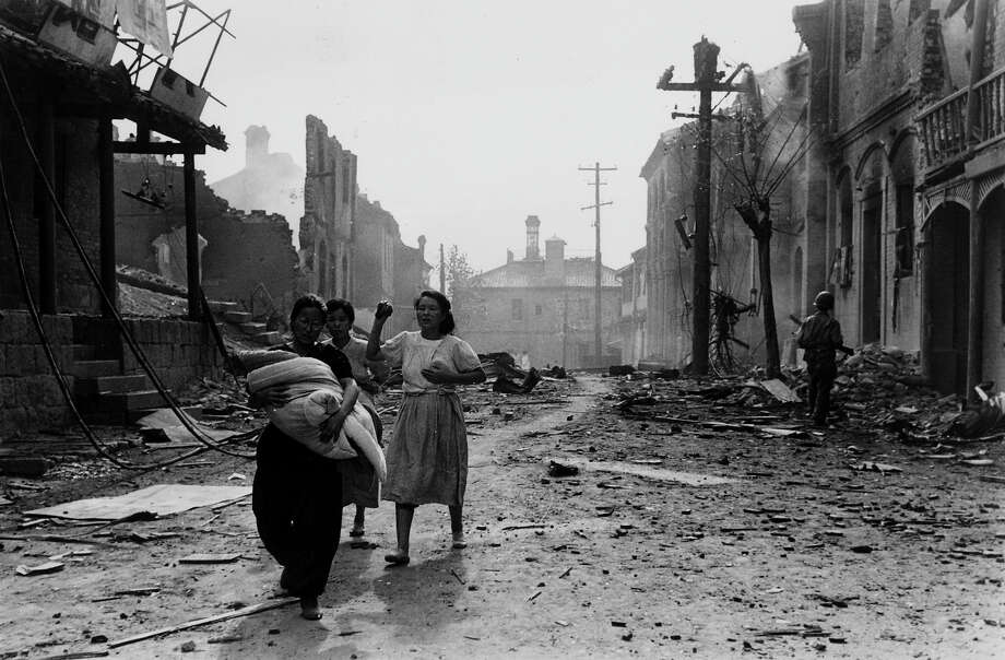 Korean refugees threading their way through the bomb devastated streets of Inchon, after an American attack on the port. Photo: Bert Hardy, Getty Images / Picture Post