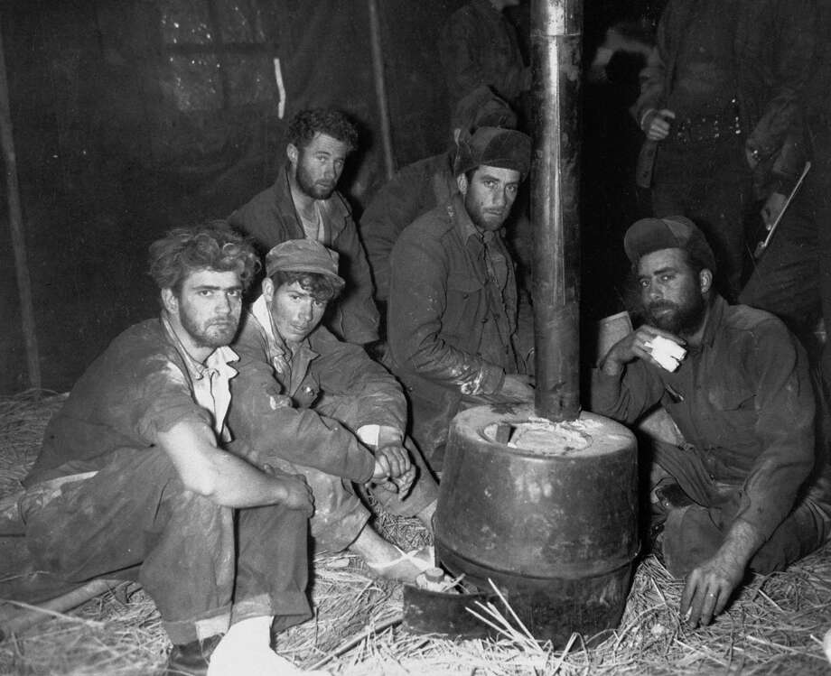 Former American & Australian POWs warming themselves before stove in 24th Division medical clearing station after being returned to US lines by Chinese Communists, during Korean War. Photo: Sfc. Al Chang, Time & Life Pictures/Getty Image / Time Life Pictures