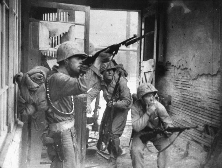 Fighting as part of United Nation forces, an American soldier advances w. rifle poised, as others duck for cover during street combat in the Korean War. Photo: And Romanowski Strickland, Time & Life Pictures/Getty Image / Time Life Pictures