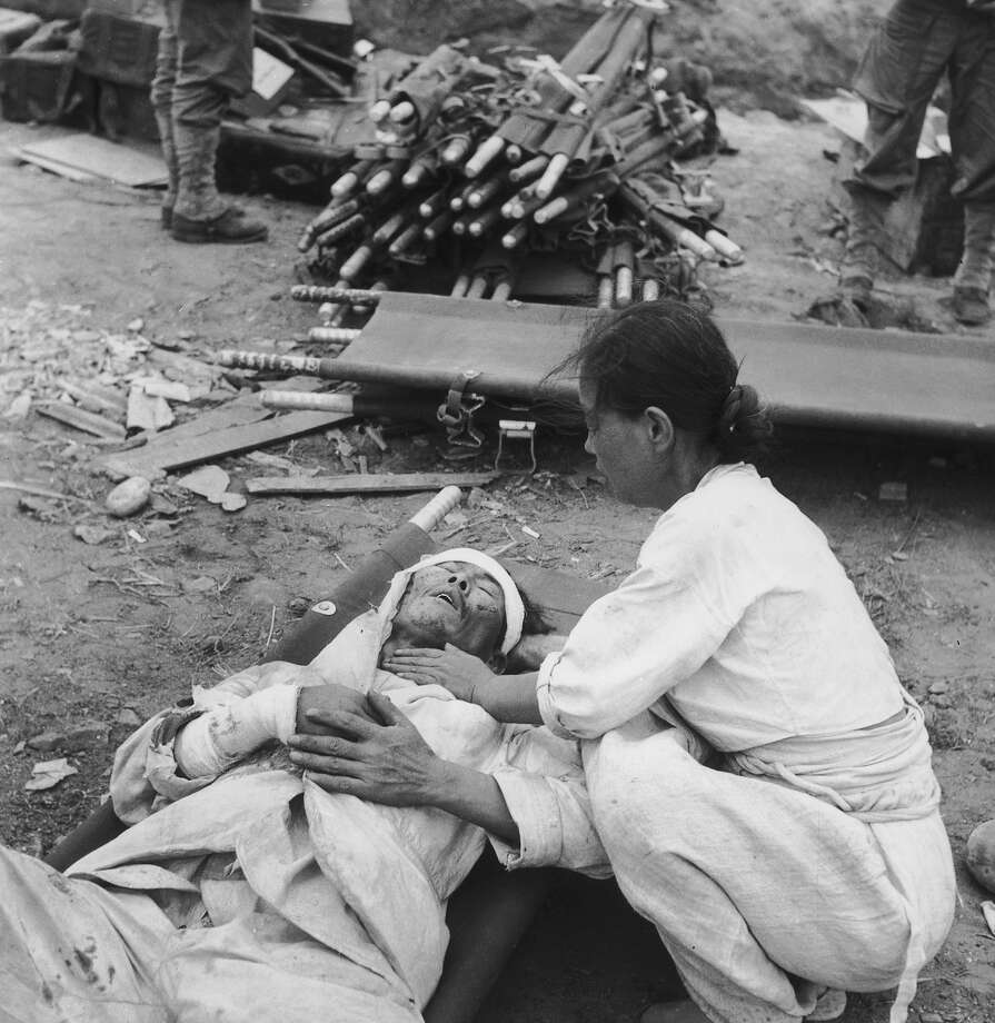 A Korean woman attending an injured man following the American invasion and capture of the port of Inchon, Korea, during the Korean War, September 1950. Photo: Bert Hardy, Getty Images / 2008 Getty Images