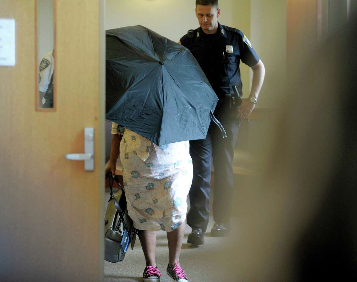 The mother of Audrea Gause uses an umbrella to hide herself as she leaves Troy City Court following a hearing on her daughter on Tuesday, July 23, 2013 in Troy, NY. Audrea Gause is accused of trying to steal $480,000 from the fund for victims of the Boston marathon bombing. (Paul Buckowski / Times Union)