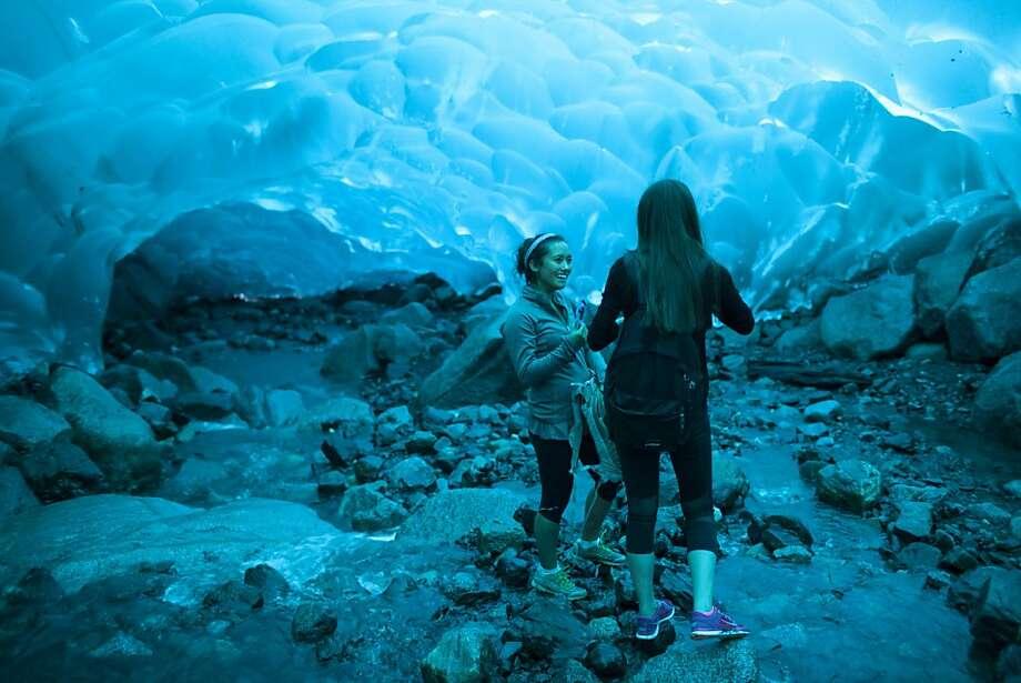 Solana Ashe (left) and Asena Uyguner visit the Mendenhall Glacier's ice caves near Juneau. Photo: Matthew Ryan Williams, New York Times