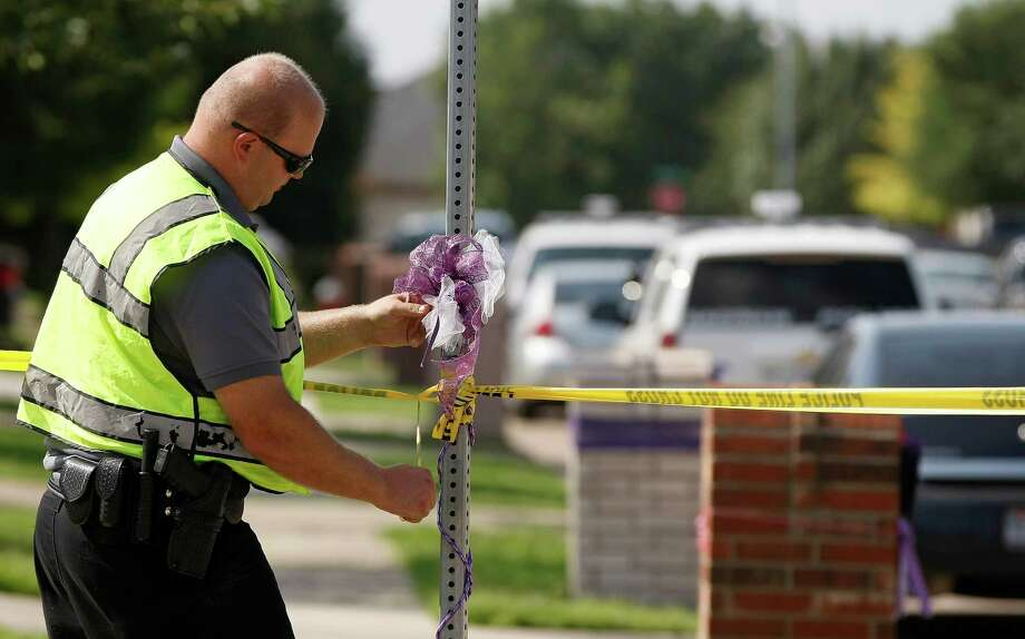 An officer tapes off  the scene of an officer involved shooting Tuesday, July 23, 2013, in Saginaw, Texas.  The officer was shot as he served a search warrant in an investigation into the killing of a 6-year-old girl whose naked, bound body was found wrapped in a tarp on the corner of a North Texas residential street, police said. Saginaw police spokesman Damon Ing said a person at the house where officers were serving the warrant was also shot.   (AP Photo/The Fort Worth Star-Telegram, Khampha Bouaphanh)  MAGS OUT; (FORT WORTH WEEKLY, 360 WEST) Photo: Khampha Bouaphanh, MBI / Fort Worth Star-Telegram