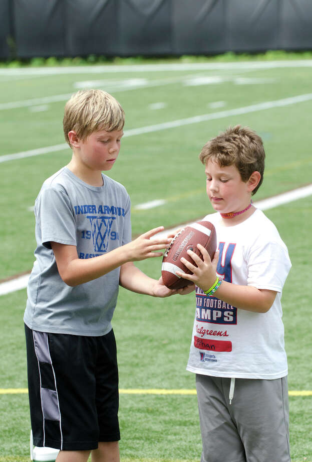 Griffin Koch, 10, of New Canaan, shows his cousin, Ethan Kaufman, 7, of Rowayton, how to hold a football during the New York Giants Youth Football Camp at St. Lukes School in New Canaan on Tuesday, July 23, 2013. Photo: Amy Mortensen / Connecticut Post Freelance