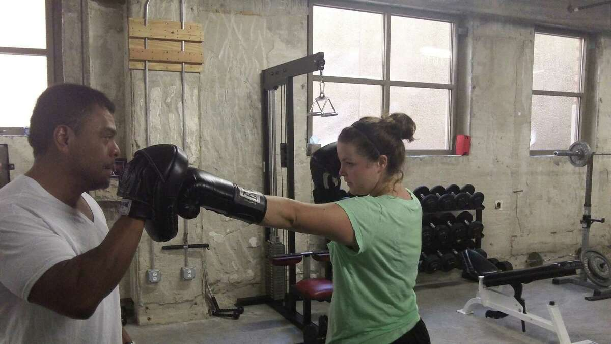 Elementary school computer teacher Jessica Young, right, practices boxing maneuvers three times a week under the tutelage of Frank Elizondo, left, at the Catayst Gym.