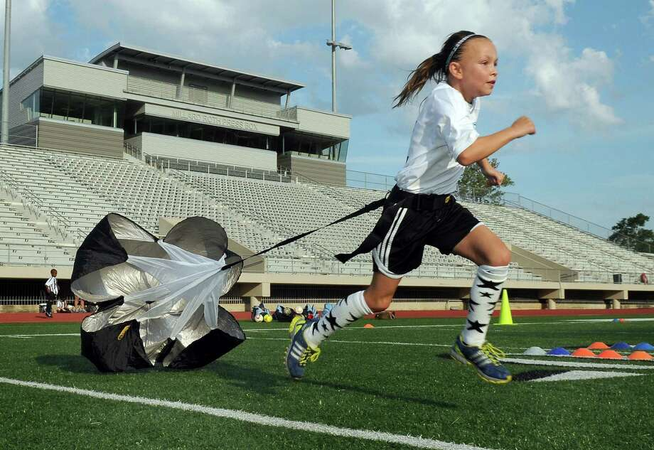 Alexa Riddle, 10, works on her wind sprints with a parachute during a Klein Soccer Club team practice at Klein Memorial Stadium. Photo: Jerry Baker, Freelance
