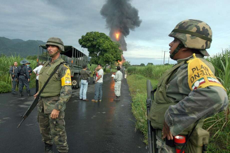 Army soldiers stand on a road as a fire rages near the town of Omealca, in the gulf state of Veracruz, Mexico, Monday, Sept. 10, 2007. Six explosions believed to be the result of sabotage ripped natural gas pipelines, prompting authorities to evacuate thousands of people and shut down two highways. Photo: Luis Monroy-STR, AP