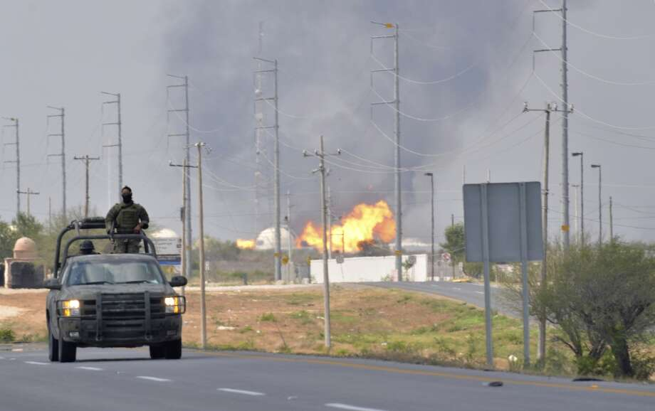 A Mexican army vehicle patrols on a road as fire and smoke rise from a gas pipeline distribution center in Reynosa, Mexico near Mexico's border with the United States, Tuesday Sept. 18, 2012. Ten people were killed during the incident. Photo: El Manana De Reynosa, Associated Press