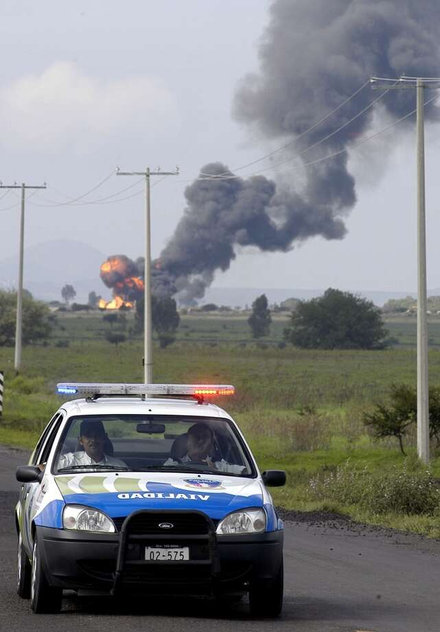 Smoke and flames from an explosion at a gas pipeline are seen in the background  as a Mexican police car drives by  near Queretaro, Mexico, Tuesday July 10,  2007. Photo: STR, AP