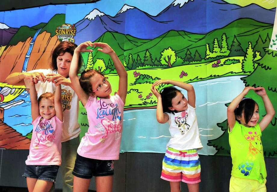 Theresa Talluto, second from left, coaches campers preparing a skit. From left are Sofia Tallutu, 5; Madelene Talluto, 7; Kate Hugo, 6; and Rachel Hugo, 4, during Sonrise Vacation Bible School St. Rose of Lima, in Newtown, Conn. Monday, July 22, 2013. Photo: Michael Duffy / The News-Times