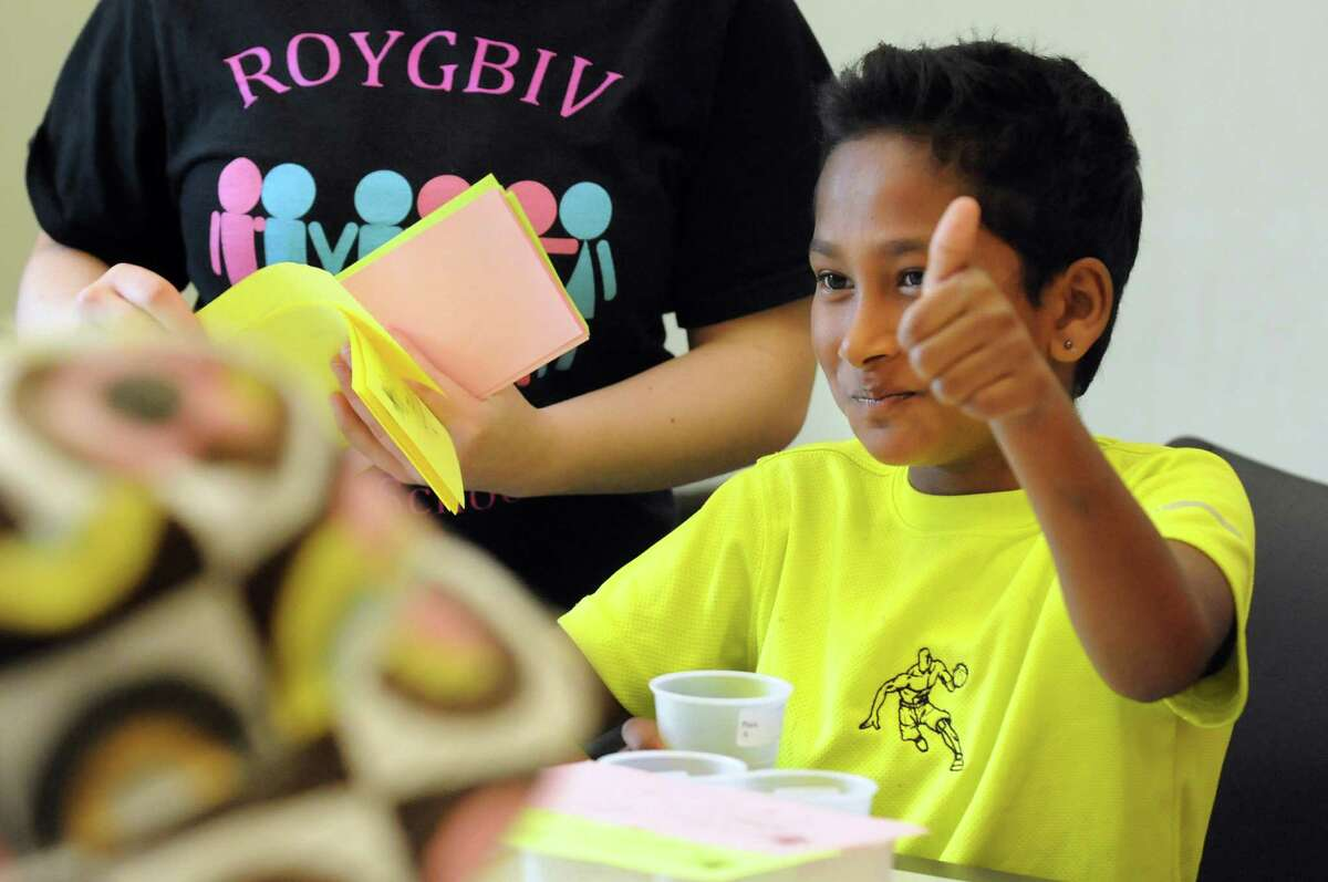 Ujwal Darjee, 10, of Albany shows his approval during a Potato Chip Tasting on Tuesday, July 23, 2013, at the Pine Hills Branch Library in Albany, N.Y. Children tasted plain, barbecue and sour cream chips from Price Chopper brand, Lays, Wise and Utz. Utz sour cream potato chips were the overall winner. (Cindy Schultz / Times Union)