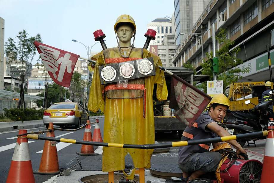 Scareperson: A figure warns traffic and passers-by of an open manhole in Taipei. Photo: Wally Santana, Associated Press