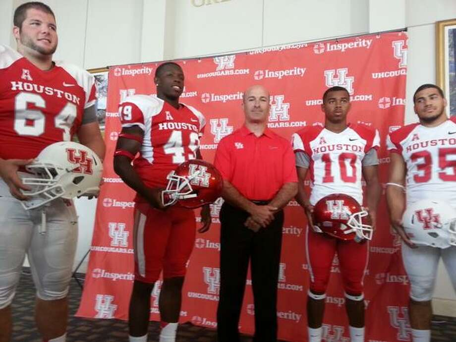 With head coach Tony Levine in the center, players Ty Cloud (64), Derrick Mathews (49), Zach McMillian (10) and Kenneth Farrow (35) model the Coogs uniform combinations. Photo: Joseph Duarte, Chronicle