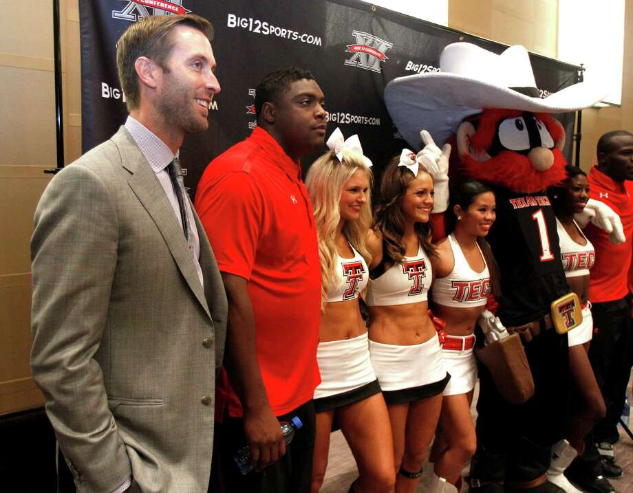Texas Tech football coach Kliff Kingsbury, left, and defensive end Kerry Hyder pose for a photo with cheerleaders following the Big 12 Conference Football Media Days Monday, July 22, 2013 in Dallas.  (AP Photo/Tim Sharp) Photo: TIM SHARP, Associated Press / FR62992 AP