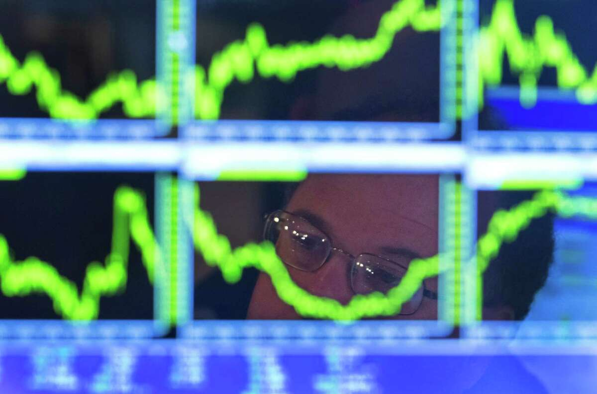 In this Monday, July 22, 2013, photo, Specialist Douglas Johnson is reflected in a screen at his post on the floor of the New York Stock Exchange. A mix of good and bad earnings reports from big companies kept the stock market treading water in early trading Tuesday, July 23, 2013. (AP Photo/Richard Drew) ORG XMIT: NYBZ117