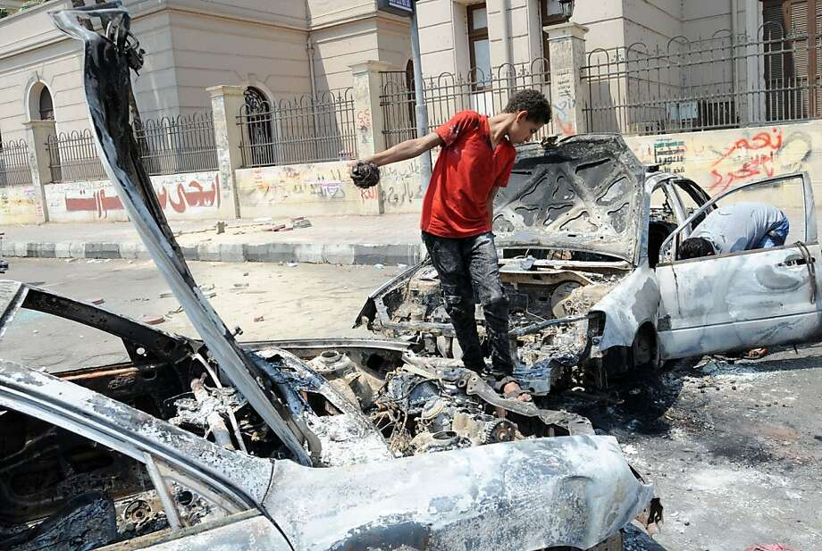 An Egyptian youth near Cairo University checks out a burned car, a casualty of the recent clashes between supporters of former President Mohammed Morsi and his opponents. Photo: Fayez Nureldine, AFP/Getty Images