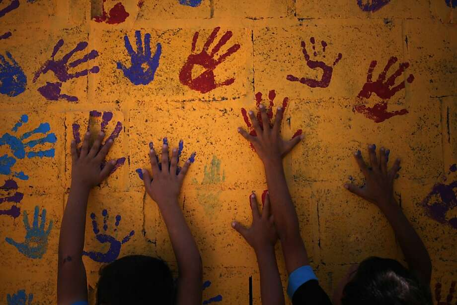 Young Syrian refugees touch colorful hand prints on a mural that they made on one of the public bathrooms, at Zaatari refugee camp, near the Syrian border, in Mafraq, Jordan, Tuesday, July 23, 2013. Most of the trailers and tents match the beige color of the swirling sand surrounding the Zaatari refugee camp, home to about 120,000 Syrians who fled the nearly three-year war still gripping the nation. Slowly though, that's changing with the help of a U.S.-based artist who is leading children haunted by the conflict to paint buildings and walls at the crowded camp with murals expressing their lives and hopes.(AP Photo/Mohammad Hannon) Photo: Mohammad Hannon, Associated Press