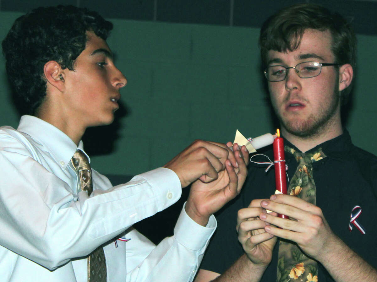 French Honor Society treasurer Zachary Polley, left, passes the ceremonial flame to inductee Lawrence Andrea at New Milford High School. June 2013 Courtesy of Barbara Polley