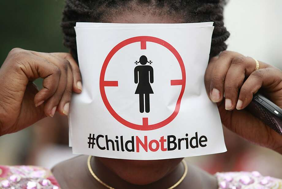 In this photo taken on Saturday, July 20, 2013, a woman protests against underage marriages in Lagos, Nigeria. Nigeria's secular and Islamic laws clashed when a senator notorious for marrying a 14-year-old filibustered a vote to amend the constitution by insisting that a girl child comes of age when she marries, not at 18. Enraged activists are demanding the senate revisit the vote, asking how a known pedophile could get away with subverting the country's constitution. (AP Photo/Sunday Alamba) Photo: Sunday Alamba, Associated Press