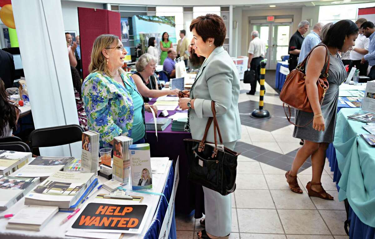 Teresa Scicchitani, left, of New York Life, speaks with communication authority Lisa Giruzzi at the SmAlbany small business expo and job fair at the Albany NanoTech complex Wednesday July 17, 2013, in Albany, N.Y. (John Carl D'Annibale / Times Union)