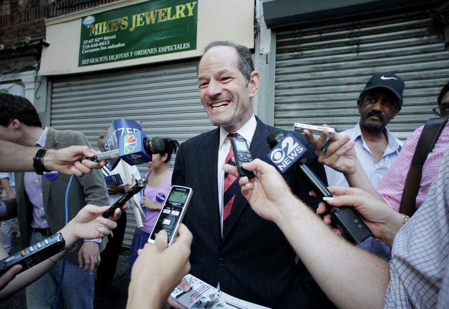 Eliot Spitzer, center, a candidate for New York City comptroller, talks with members of the media as he campaigns in the Jackson Heights neighborhood of the Queens borough of New York, Tuesday, July 23, 2013. Spitzer, who resigned as New York governor in 2008 after admitting he paid for sex with prostitutes, is now attempting a political comeback and is ahead of opponent Scott Stringer in the polls. (AP Photo/Mark Lennihan) ORG XMIT: NYML105 Photo: Mark Lennihan / AP