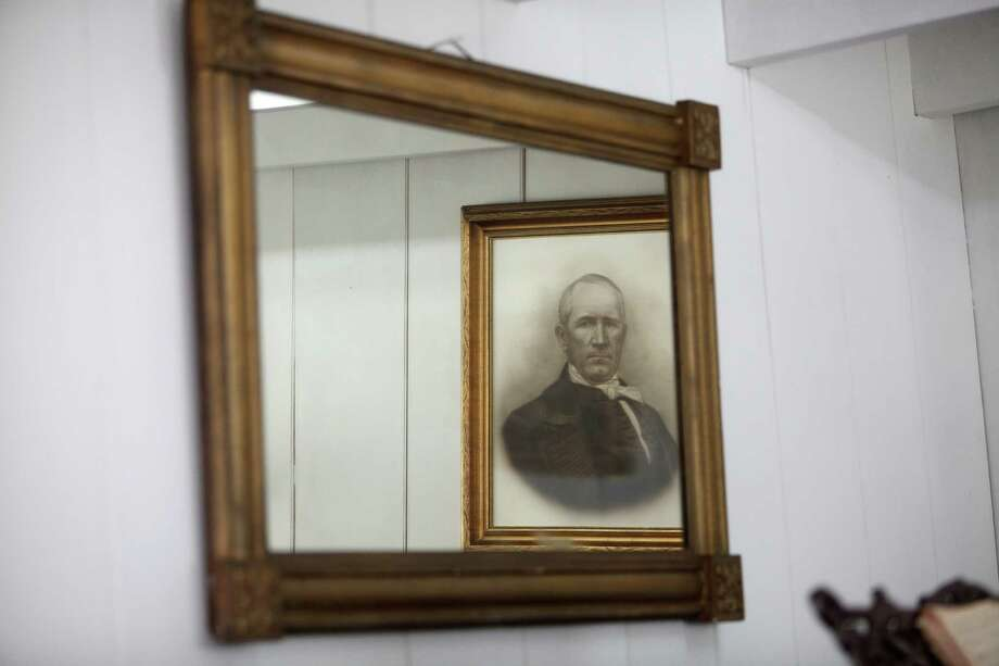 An original mirror reflects a portrait of Sam Houston in his home named 'Woodland Home'. Photo: Mayra Beltran / © 2013 Houston Chronicle