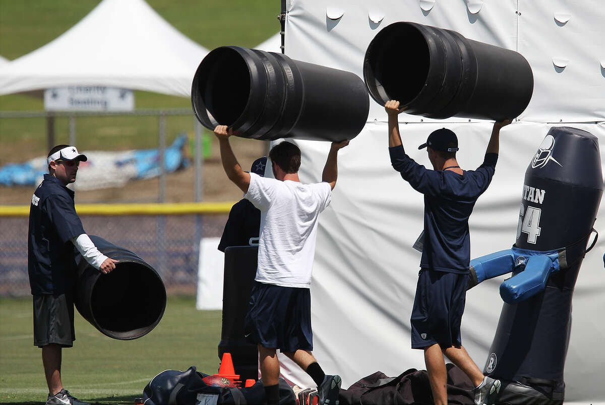 Assistants put away plastic garbage cans used during special teams drills during the morning session of the 2013 Dallas Cowboys training camp on Tuesday, July 23, 2013 in Oxnard.