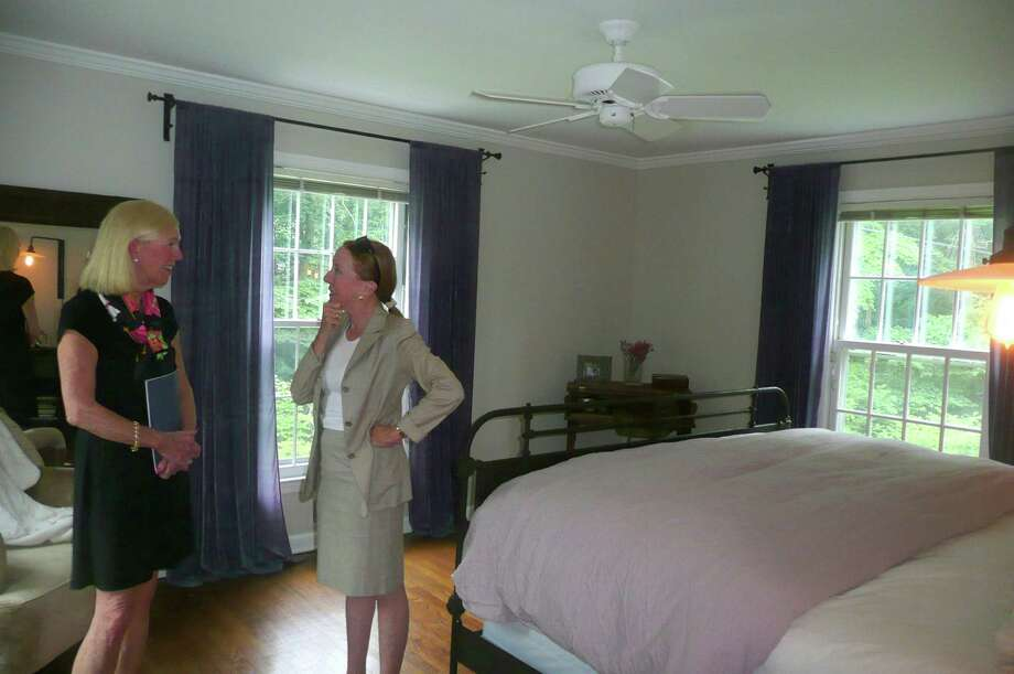 Realtor Kathryn Anderson Adams, right, tells prospective buyer Linnie Pickering about a benefit of the oversized windows in the master bedroom of the home at 244 Stanwich Road. âÄúYou can open the window at night and hear the waterfall from the brook down below,âÄù she notes. Photo: Anne W. Semmes