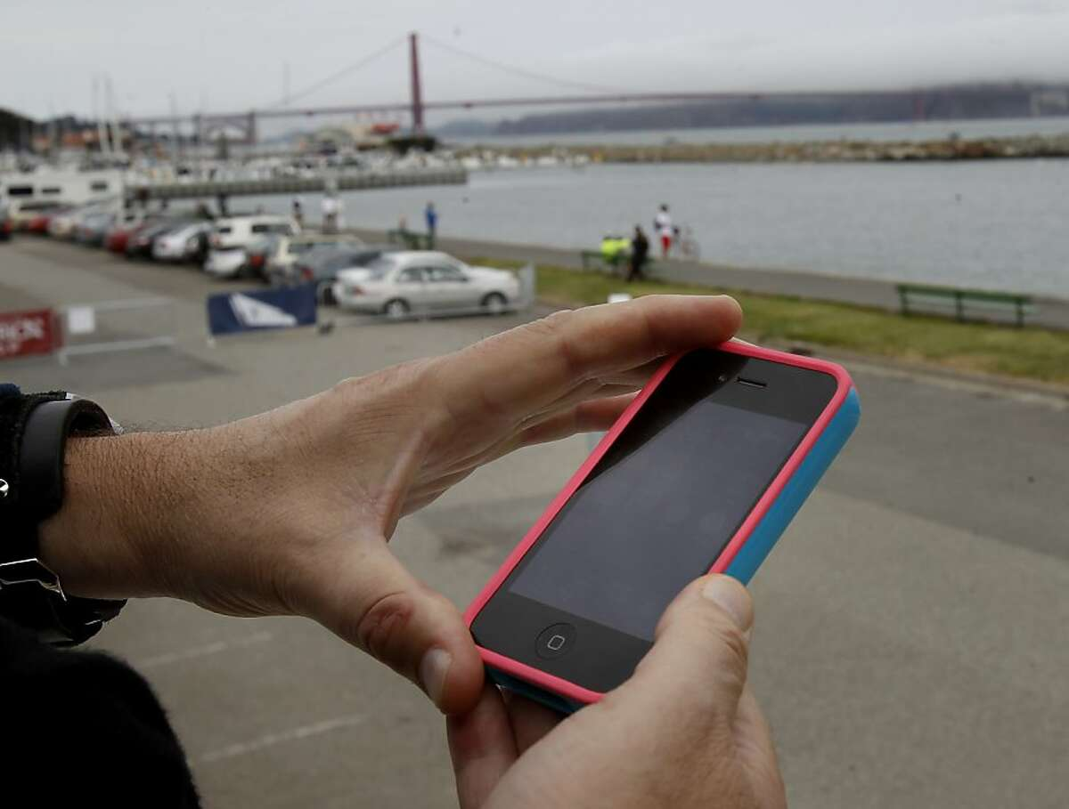 At Marina Green, an Americas Cup fan uses his smart phone for information about the upcoming race Tuesday July 23, 2013. Marina Green is one of the locations to get a new hot spot. Google will pay to install wireless access in 31 San Francisco parks, a donation brokered by Supervisor Mark Farrell, which will bring hot spots to every district of the city.