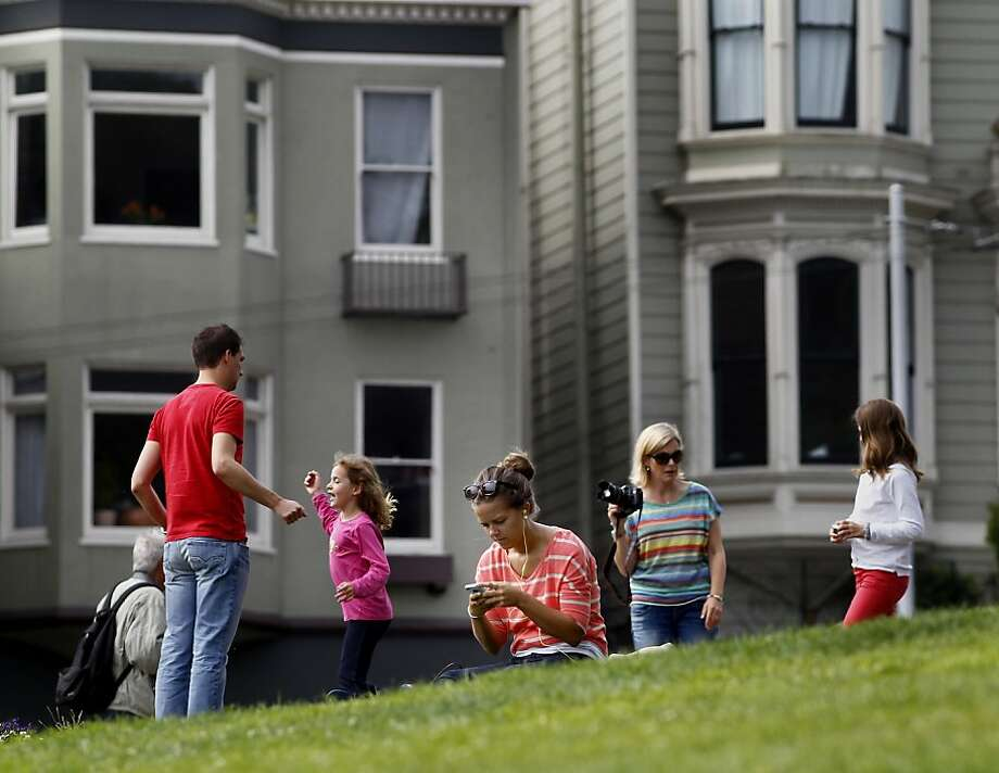 Ali LeBel (foreground) adjusts her smart phone in Alamo Square Tuesday July 23, 2013, one of the locations where new wireless will be added.  Google will pay to install wireless access in 31 San Francisco parks, a donation brokered by Supervisor Mark Farrell, which will bring hot spots to every district of the city. Photo: Brant Ward, The Chronicle