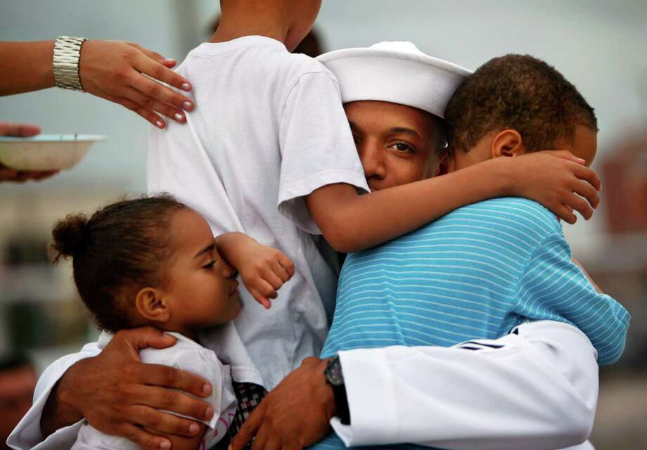 Petty Officer 1st Class Malik Leslie hugs his children, from left, Layla, 3, Malik, 7, and Seth, 5, before his deployment on the Harry S. Truman from Norfolk Naval Station, Va., for a nine-month cruise to the Persian Gulf on Monday, July 22, 2013. Photo: Stephen M. Katz, Associated Press / The Virginian-Pilot