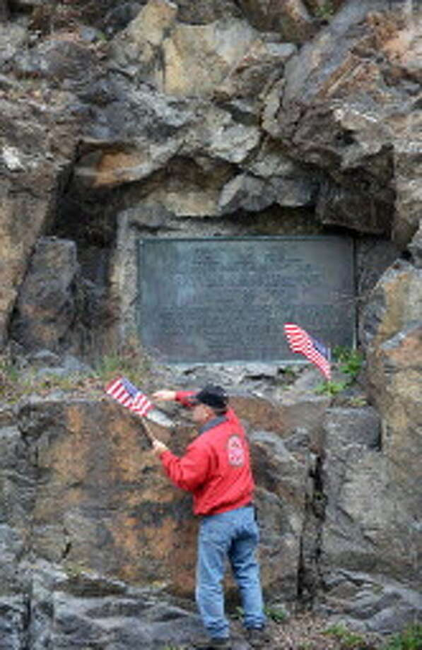 Earlier this year, life-long Fort Ann resident George Sherwood places American flags at the 1927 historic marker embedded in the rock face of Battle Hill along Route 4, in Fort Ann, where the British and American forces clashed just before the Battle of Saratoga in 1777. The historic battlefield was purchased by a private developer, who has applied to mine a stone quarry on the site. (John Carl D'Annibale / Times Union)