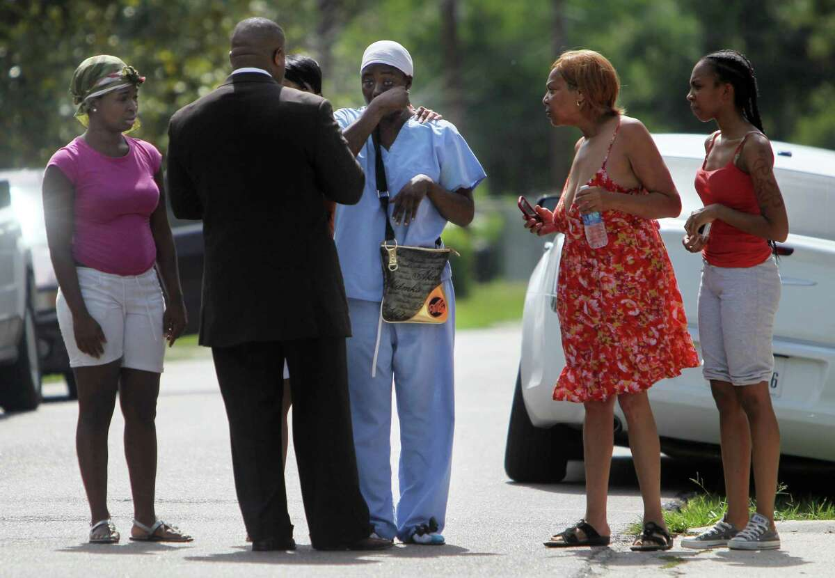"""Shanequia McDonald, surrounded by friends, confers Tuesday with Quanell X before a news conference where the community activist described a fatal gas station shooting as a """"classic stand your ground"""" case."""