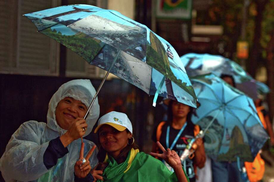 Pilgrims walk under the rain in Rio de Janeiro, Brazil during the World Youth Day (WYD) on July 23, 2013. Brazil scrambled on Tuesday to beef up security around Pope Francis after he was mobbed by adulating crowds upon his arrival on a landmark visit to the country. AFP PHOTO / GABRIEL BOUYSGABRIEL BOUYS/AFP/Getty Images Photo: GABRIEL BOUYS / AFP