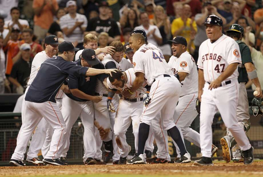July 23: Astros 5, A's 4Astros shortstop Jonathan Villar is mobbed by teammates after scoring the winning run in the bottom of the ninth inning against the A's. Photo: Thomas B. Shea, For The Chronicle