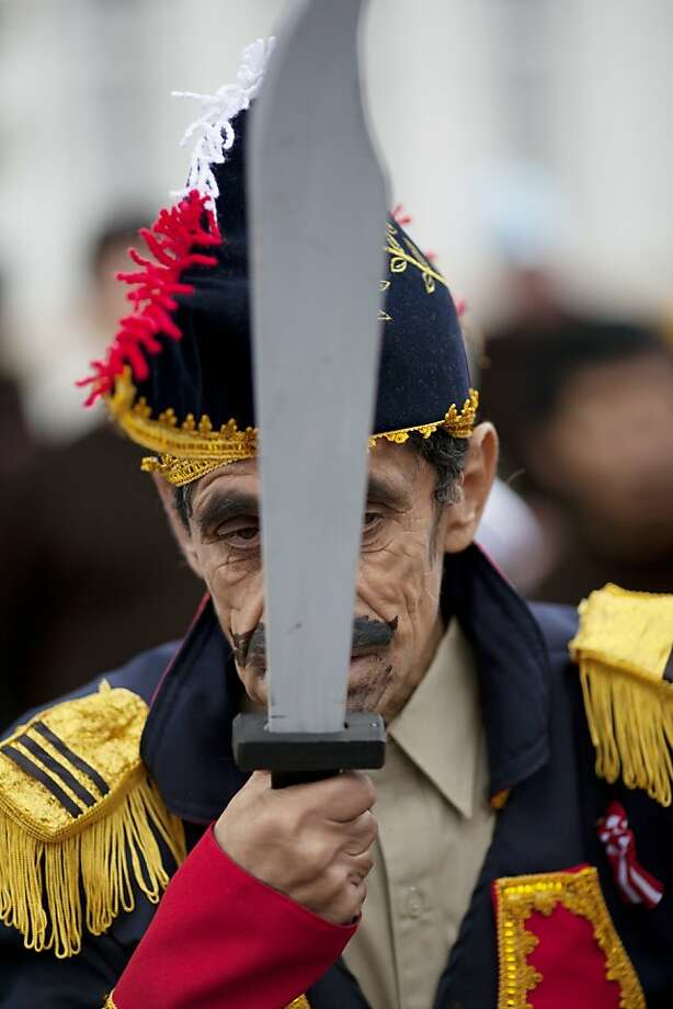 Julio Peliaranda, dressed as Peruvian independence hero Jose de San Martin, holds up his wooden sword after marching in the hospital's own Peruvian Independence Day parade at the psychiatric hospital in Lima, Peru, Tuesday, July 23, 2013. The parade was organized ahead of Peru's official Independence Day celebrations on July 28.(AP Photo/Rodrigo Abd) Photo: Rodrigo Abd, Associated Press