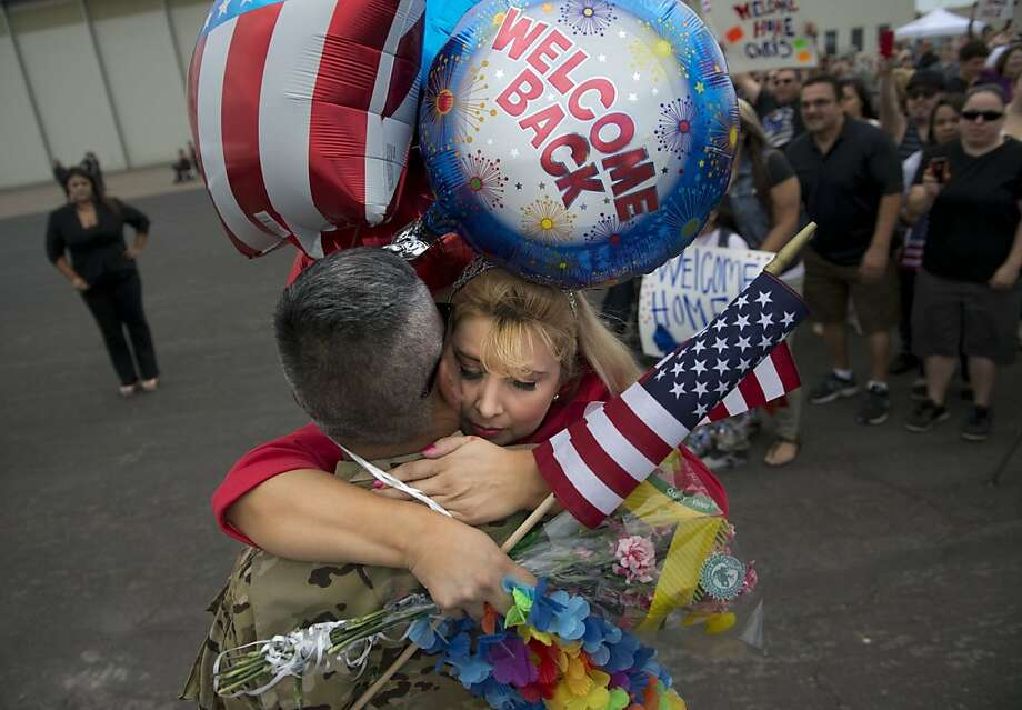 Hjalma Diaz, of Manteca, California, gets a hug from his wife, Tammy, after he returned from Afghanistan with about 120 soldiers from a California Army National Guard Chinook helicopter unit after a year-long deployment on Tuesday, July 23, 2013, in Stockton, California. (Hector Amezcua/Sacramento Bee/MCT) Photo: Hector Amezcua, McClatchy-Tribune News Service
