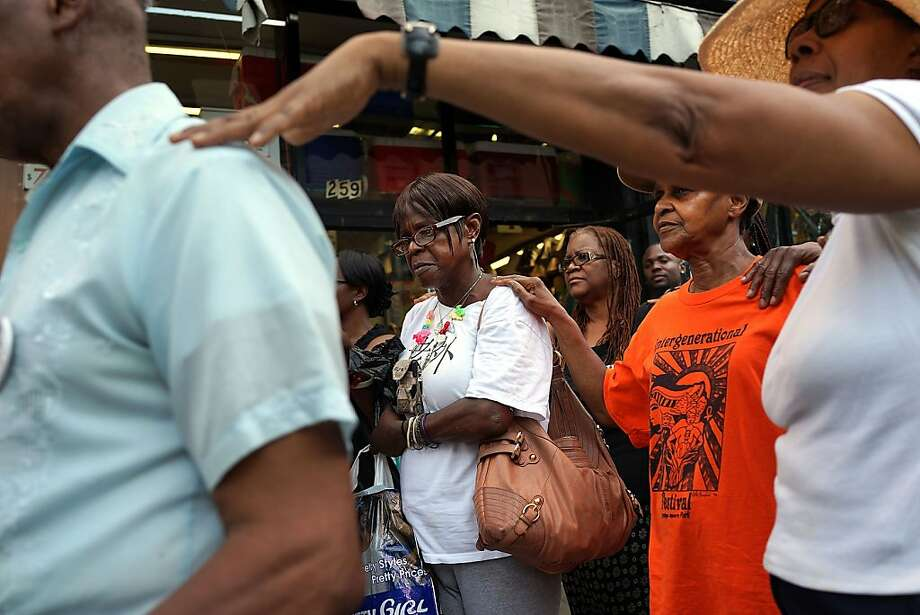 NEW YORK, NY - JULY 23:  People pray at a rally near where four people were recently shot on July 23, 2013 in the Brooklyn borough of New York City. Following a weekend in which 11 people were shot and wounded in Brooklyn alone, members of Save Our Streets (S.O.S.), a community-based effort to end gun violence, held a vigil and rally near where the four people were shot in Crown Heights on Sunday night. In response  to the recent spate of shootings, the New York Police Department (NYPD) has set up stationary observation towers, added patrols and put additional plainclothes officers in high crime neighborhoods. S.O.S. holds the gatherings at all shooting locations in Crown Heights to draw attention to the violence and to encourage community response to the shootings.  (Photo by Spencer Platt/Getty Images) Photo: Spencer Platt, Getty Images