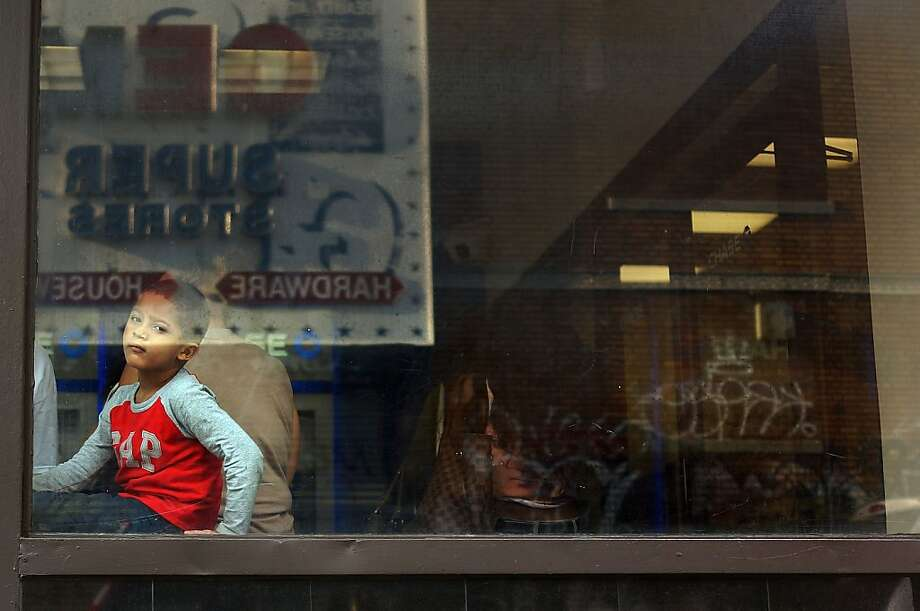 NEW YORK, NY - JULY 23:  A child looks out of a bank's window near where four people were recently shot on July 23, 2013 in the Brooklyn borough of New York City. Following a weekend in which 11 people were shot and wounded in Brooklyn alone, members of Save Our Streets (S.O.S.), a community-based effort to end gun violence, held a vigil and rally near where the four people were shot in Crown Heights on Sunday night. In response  to the recent spate of shootings, the New York Police Department (NYPD) has set up stationary observation towers, added patrols and put additional plainclothes officers in high crime neighborhoods. S.O.S. holds the gatherings at all shooting locations in Crown Heights to draw attention to the violence and to encourage community response to the shootings. (Photo by Spencer Platt/Getty Images) Photo: Spencer Platt, Getty Images