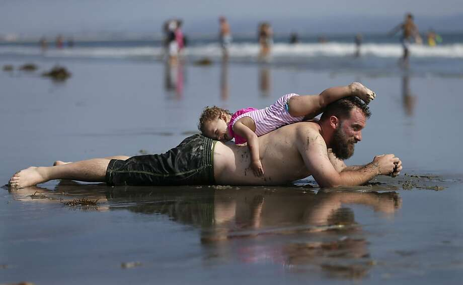 A man who did not give his name rests with his daughter on the beach under sunny skies Tuesday, July 23, 2013, in Coronado, Calif. Warm weather and blue skies brought summertime crowds to area beaches Tuesday, with more good weather forecasted on the way. (AP Photo/Gregory Bull) Photo: Gregory Bull, Associated Press