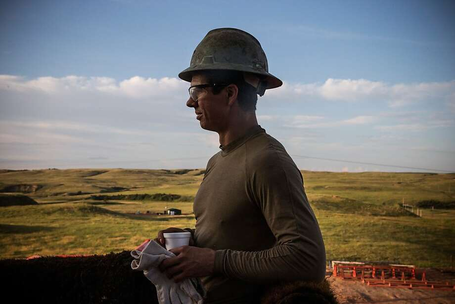 "WATFORD CITY, ND - JULY 23:  Jeff Allyn, a derrick hand with Raven Drilling, pauses with a cup of coffee while drilling for oil in the Bakken shale formation on July 23, 2013 outside Watford City, North Dakota.  North Dakota is been experiencing an oil boom in recent years, due in part to new drilling techniques including hydrolic fracturing and horizontal drilling. In April 2013, The United States Geological Survey released a new study estimating the Bakken formation and surrounding oil fields could yield up to 7.4 billion barrels of oil, doubling their estimate of 2008, which was estimated at 3.65 billion barrels of oil. ""If you're not working out here, there's no excuses. I went to prison for six years - it doesn't matter what your past is,"" Allyn said.  (Photo by Andrew Burton/Getty Images) Photo: Andrew Burton, Getty Images"