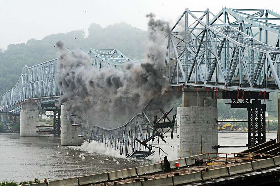 The 700-foot central span of the old Madison-Milton Bridge falls into the Ohio River on Tuesday, July 23, 2013 in Madison, Ind., after a series of controlled explosions separated it from the rest of the  superstructure. Using many small explosive charges placed at critical locations on the bridge, subcontractor Advanced Explosives Demolition Inc. (AED) detonated the charges in intervals to control the  direction of fall. The 1929 Milton-Madison Bridge will be demolished in a series of   three or four blasts about seven days apart over the next few weeks.   (AP Photo/The Madison Courier, Ken Ritchie) Photo: Ken Ritchie, Associated Press