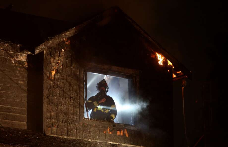A firefighter looks from a window as they work to knock down flames during a house fire. Photo: JOSHUA TRUJILLO, SEATTLEPI.COM