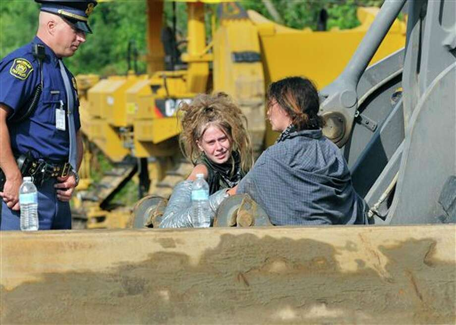 Two protesters from the Michigan Coalition Against Tar Sands (MICATS) group, who are locked by a mechanical device to heavy equipment at a Enbridge pipleline construction site, talk with a Michigan State Trooper near Stockbridge, Mich., Monday  July 22, 2013. The two were later cut free and arrested.  (AP Photo/Lansing State Journal, Rod Sanford) Photo: Rod Sanford, AP / Lansing State Journal