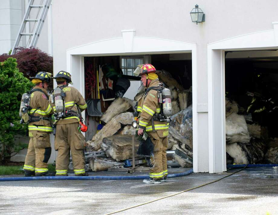 Stamford Fire and Rescue work to remove burnt insulation from the garage of Susan Cullman and John Kirby's home at 88 Saddle Rock Road in Stamford, Conn., after a fire broke out in the crawl space of the garage on Wednesday, July 24, 2013. Photo: Lindsay Perry / Stamford Advocate