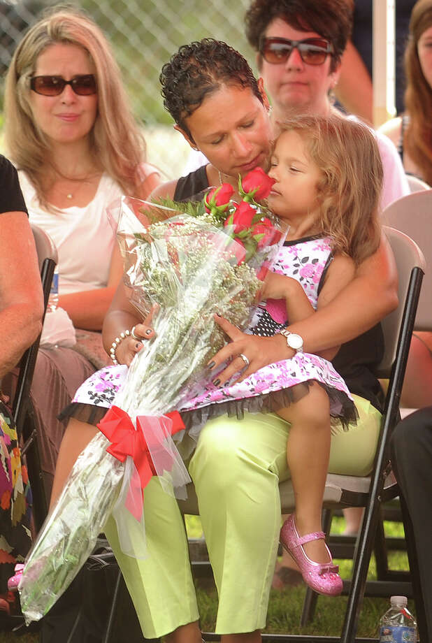 Marianne Velasquez, widow of Bridgeport fire Lt. Steven Velasquez, and her daughter, Salina, 4, receive a bouquet of flowers during a ceremony honoring Velasquez and Firefighter Michel Baik outside the Ladder 11 firehouse on Ocean Terrace in Bridgeport, Conn on Wednesday, July 24, 2013. The ceremony marked the three-year anniversary of Velasquez and Baik's deaths while fighting a multifamily house fire on Elmwood Avenue on Bridgeport's West Side. Photo: Brian A. Pounds / Connecticut Post