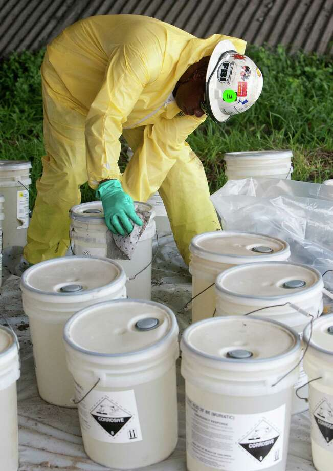 A crew cleans up hydrochloric acid on FM 2351 near the Gulf Freeway,  Wednesday, July 24, 2013, in Houston. Westbound and eastbound FM 2351 were temporarily closed while crews clean up the spill. The westbound lanes opened about 30 minutes later. Photo: Cody Duty, Houston Chronicle / © 2013 Houston Chronicle