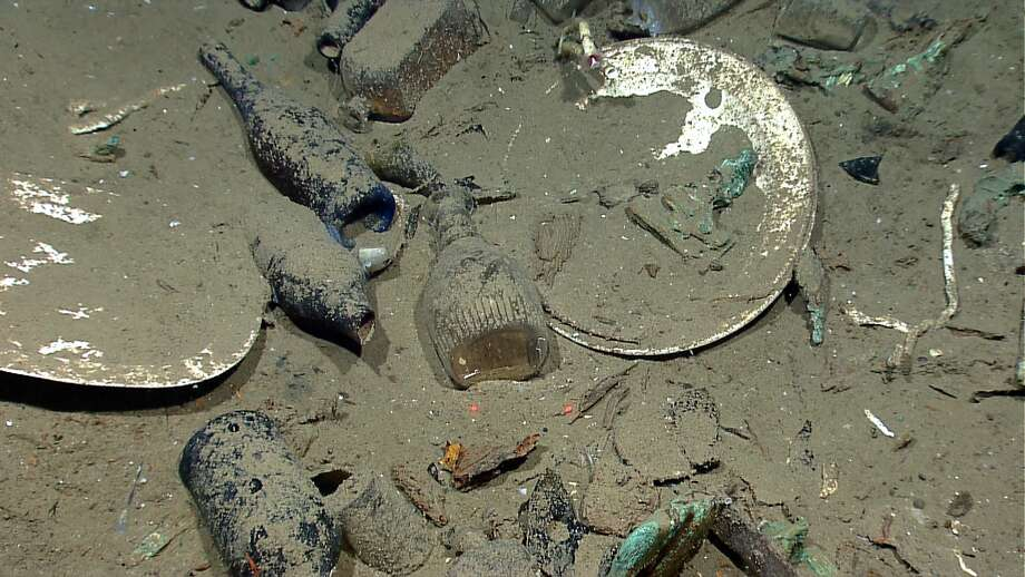 A variety of artifacts inside the ship's hull relates either to daily life on board or to the ship's cargo. Artifacts include ceramic plates, platters, and bowls; and glass liquor, wine, medicine, and food storage bottles of many shapes and colors (some with the contents still sealed inside).(Credit: NOAA Okeanos Explorer Program.)